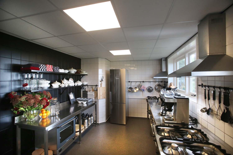 De keuken van de groepsaccommodatie, met o.a. twee fornuizen, koffiezetapparaten en een grote koelkast